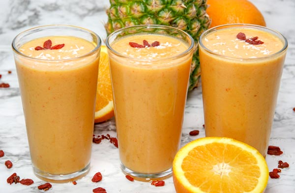 three glasses of dreamsicle smoothie side by side topped with goji berries