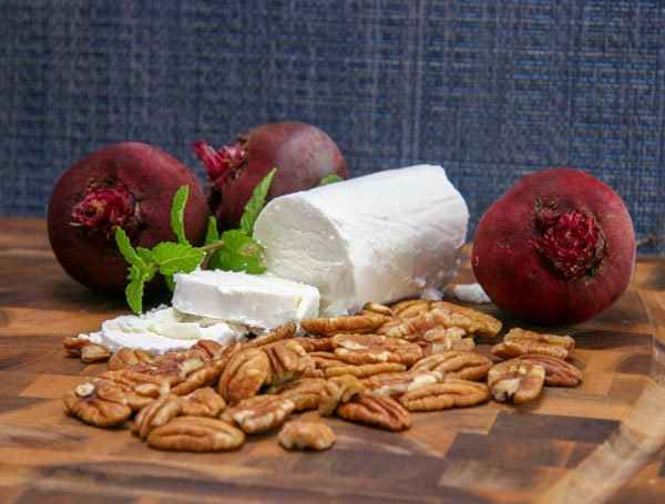 fresh beets, sprigs of mint, sliced chevre cheese, and pecans on a cutting board