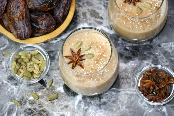 topdown shot of a glass of spiced date smoothie garnished with cardamom and star anise