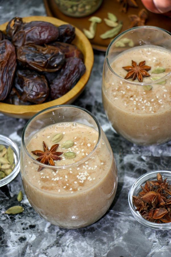 two glasses of spiced date smoothie garnished with spices with a bowl of dates in the background