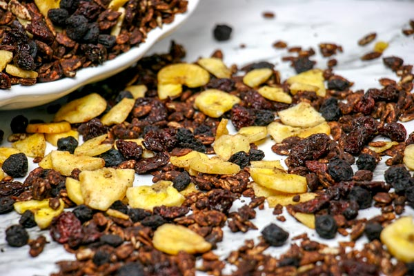 chocolate banana berry granola snack mix scattered across white marble counter