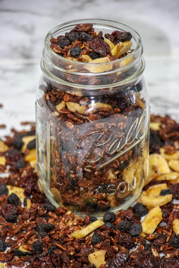 mason jar filled with blueberry and cherry banana chocolate granola snack mix with more around the base of the jar