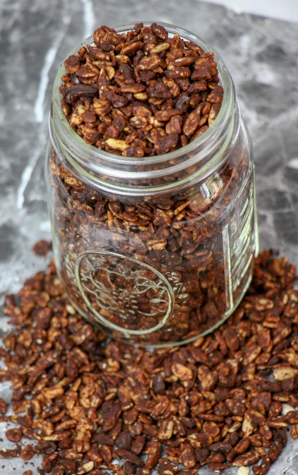 allergy friendly healthy homemade chocolate granola in mason jar with granola surrounding