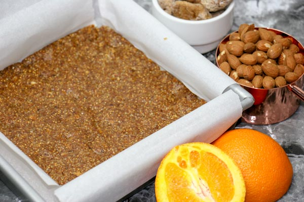 packed citrus fig and almond bars before cutting in pan with almonds, figs, and oranges nearby