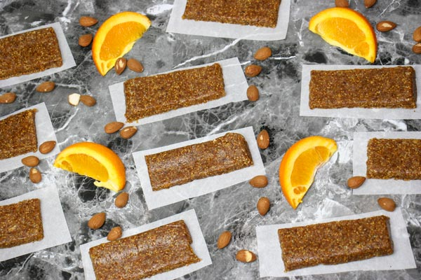 citrus fig and almond snack bars on countertop spread out with sliced oranges and almonds