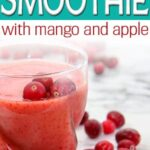 glass of mango cranberry smoothie surrounded by fresh cranberries and sliced mango