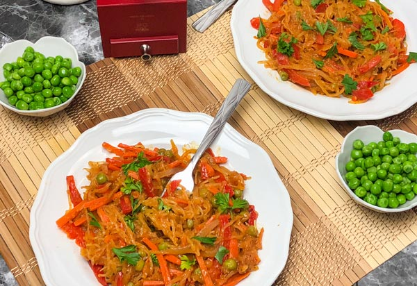 two plates of spaghetti squash vegetable curry with small bowls of peas on a bamboo mat