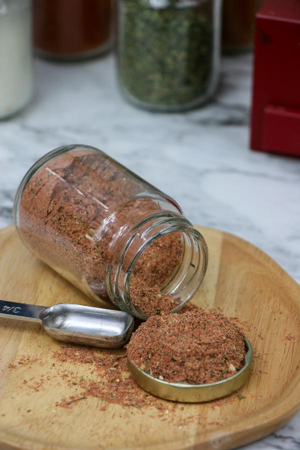 Jar of cajun seasoning on a plate with a measuring spoon next to it