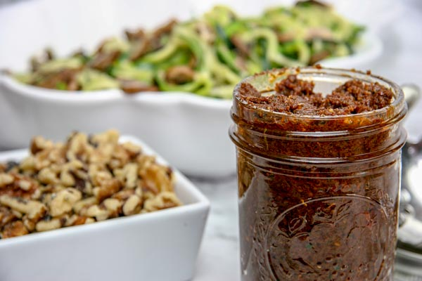 sun dried tomato walnut pesto with zoodles and mushrooms in the background