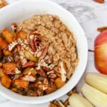 bowl of spiced oats topped with spiced apples, pecans, and golden raisins for apple pie oatmeal