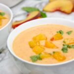 close up bowl of chilled peach soup blender, creamy blender soup with mint and chopped peaches