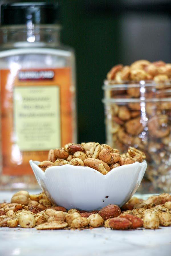 garlic herb nut mix in bowl with nuts surrounding and more nut mix in glass jar behind by spices