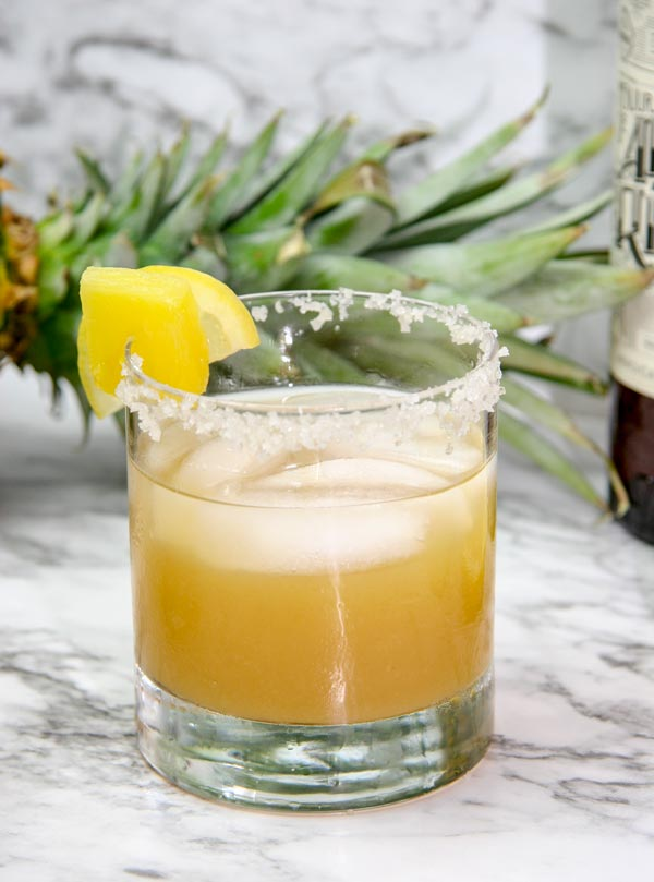 glass of pineapple margarita with ancho chile liqueur with a pineapple in the background