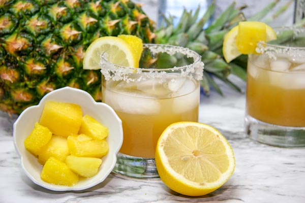 two glasses of smoky spicy pineapple margarita with a bowl of pineapple chunks and a half a lemon next to them