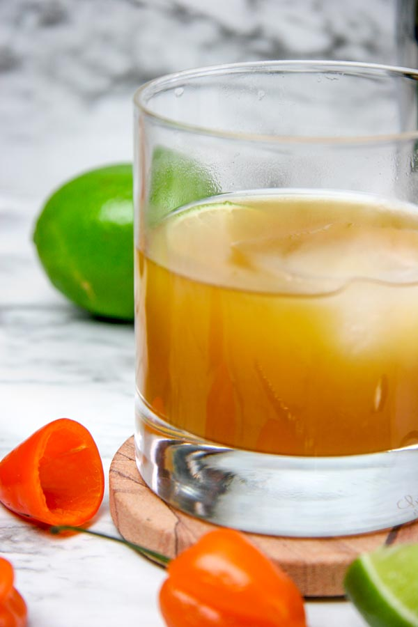 closeup of a habanero whiskey mango glass with habaneros and limes around it