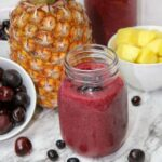 closeup of a mason jar of pineapple berry smoothie with fresh cherries and blueberries around it and a pineapple in the background