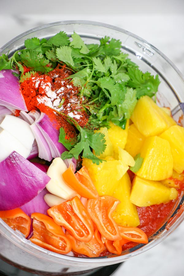 food processor full of ingredients for pineapple habanero salsa: pineapple, habaneros, tomatoes, red onion, cilantro, garlic, and spices