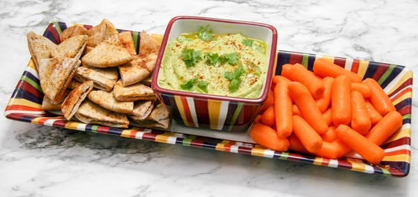 serving dish of roasted poblano hummus with pita chips and baby carrots
