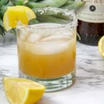 closeup of a glass of spicy pineapple margarita garnished with a lemon wedge and a pineapple chunk