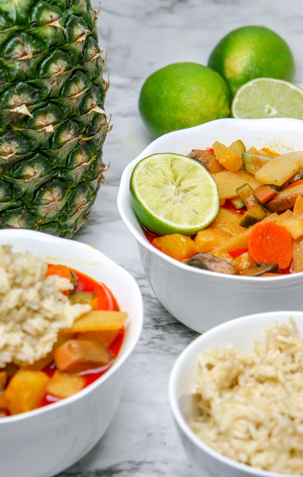 two bowls of tropical vegan pineapple curry with limes and a pineapple behind them