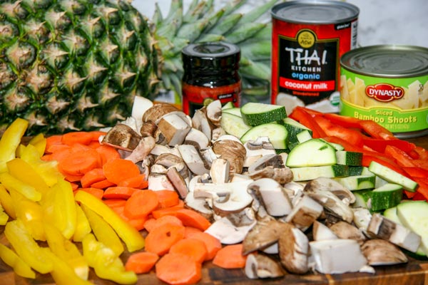 sliced bell pepper, sliced carrots, sliced mushrooms, sliced zucchini, bamboo shoots, pineapple, red curry paste, and a can of coconut milk set out on a cutting board