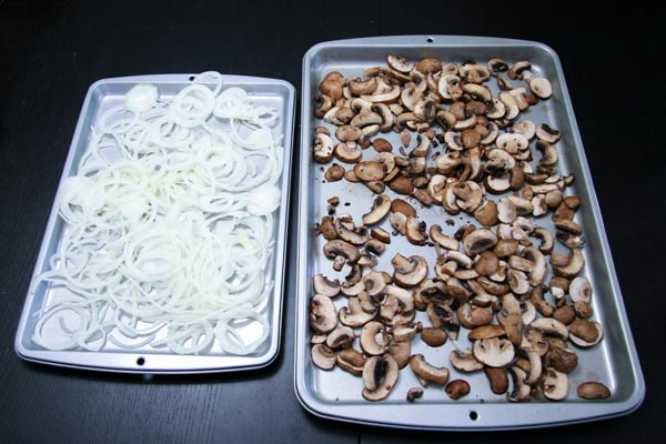 two sheet pans, one with sliced white onion and the other with sliced mushrooms