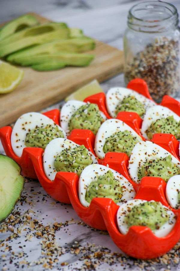 avocado everything deviled eggs in bright egg tray with everything bagel seasoning