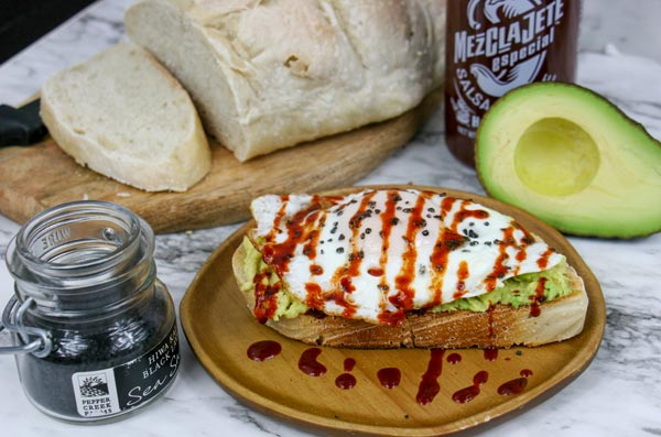 avocado toast on sourdough topped with black salt and mezclajete sauce with hot sauce bottle and an avocado in the background next to a loaf of sourdough