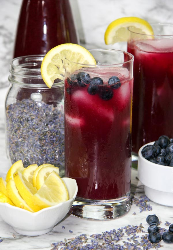 two glasses of blueberry lavender lemonade with fresh fruit, jar of lavender, and full decanter