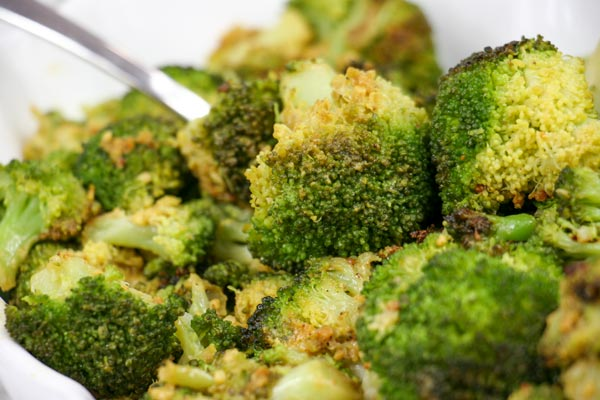 closeup of roasted broccoli with vegan cheezy garlic seasoning