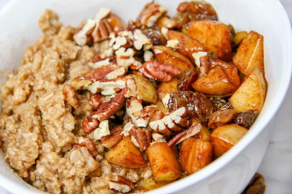 up close bowl of spiced oats with half covered in spiced apples and raisins and toasted pecans for apple pie oatmeal breakfast