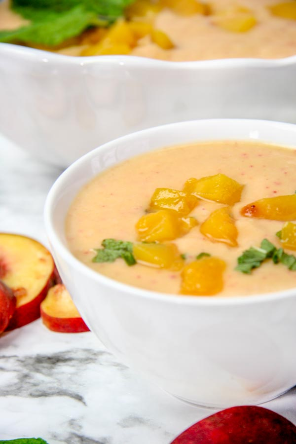 close up bowl of cold peach blender soup and larger serving bowl behind