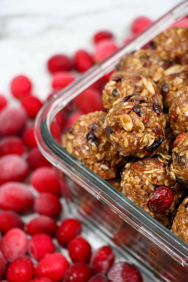 cranberry cacao energy balls in storage container with fresh cranberries surrounding