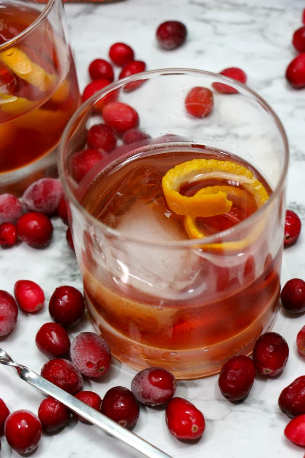 glass of cranberry vanilla whiskey cocktail with an orange twist garnishing it and cranberries around the glass