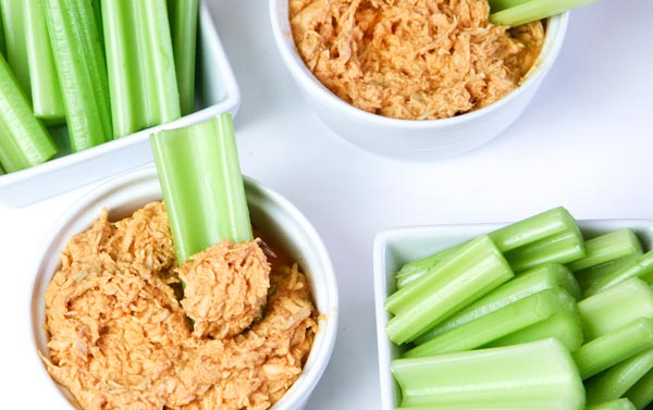 3 ingredient healthy slow cooker buffalo chicken dip in bowls with serving dishes of celery sticks