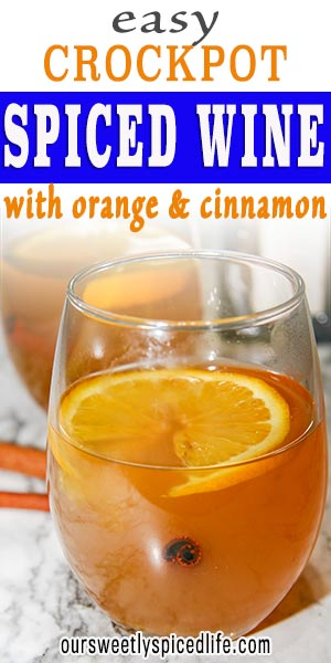 a wine glass of spiced white wine with an orange slice and a cinnamon stick garnishing it