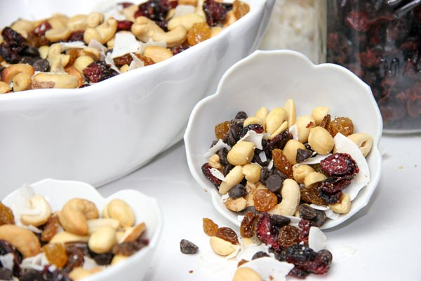 sweet and salty trail mix spilling out of flower shaped bowl with ingredients behind and more mix nearby