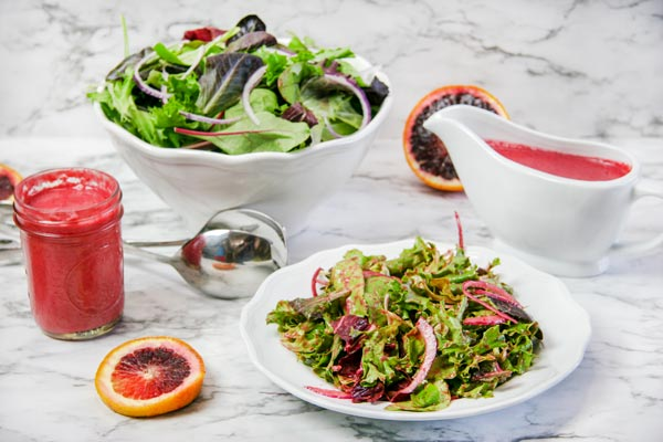 plate and bowl with side salad of spring greens, onion slices, and DIY blood orange raspberry dressing in small pitcher and glass jar