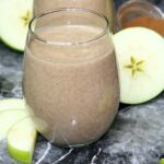 apple pie smoothie with sliced green apples nearby and small bowl of cinnamon