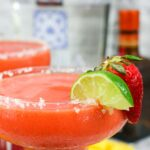close up frozen blended strawberry mango margarita garnished with lime wedge and strawberry
