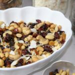 large scalloped bowl filled with sweet and salty trail mix with ingredients in mason jars in background