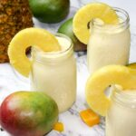 mason jars filled with mango pineapple smoothie and garnished with fresh pineapple