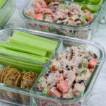 glass bento box with tuna salad, celery sticks, carrots