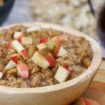 up close wooden bowl with apple cinnamon oatmeal and fresh chopped apples and cinnamon on top