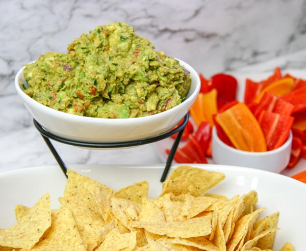 chunky homemade guacamole in chip and dip bowl with chips and bell pepper dippers