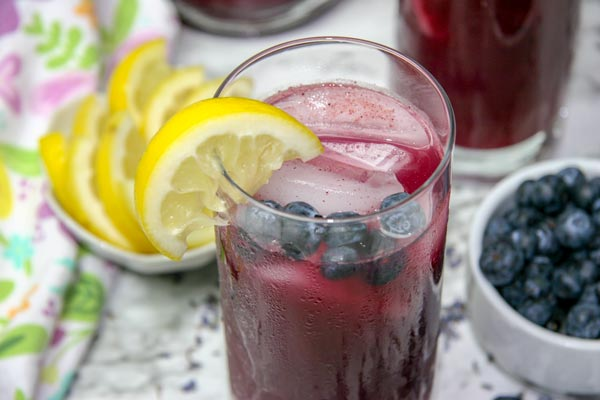 close up blueberry lavender lemonade in glass with lemon slice and blueberries