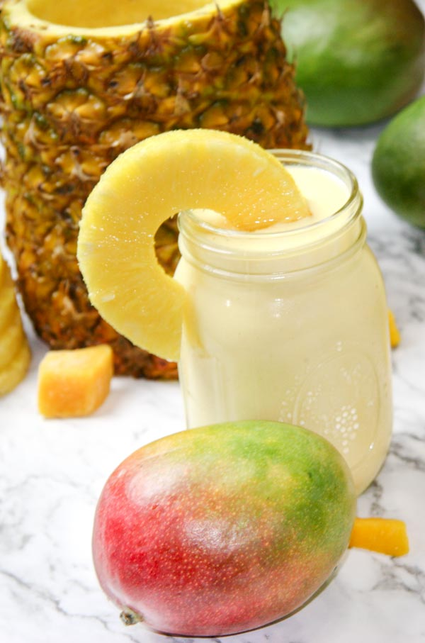 mango pina colada smoothie with pineapple background and mango nearby