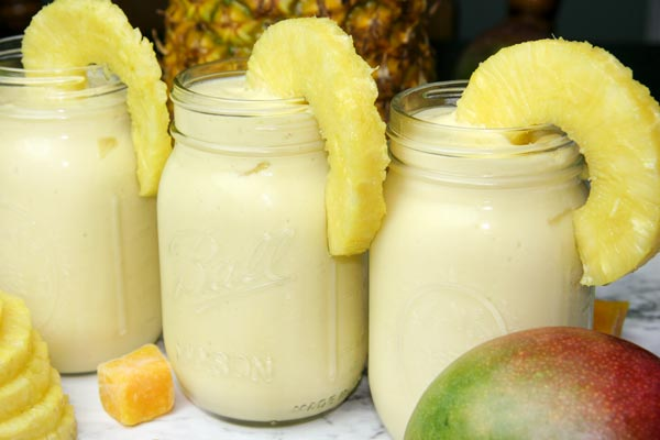 three mango pina colada smoothies in mason jars with pineapple slices