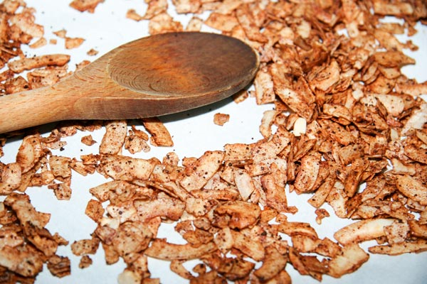 pumpkin spiced coconut chips on baking sheet with wooden spoon