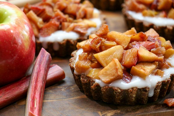 three breakfast rhubarb fruit tarts with apple and rhubarb stalks